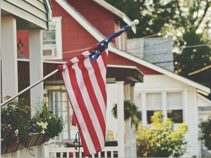 Close-up of american flag against houses
