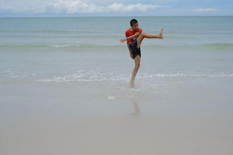 Full length of shirtless boy on beach