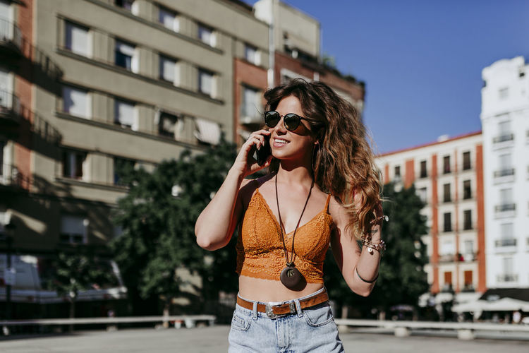 Young woman looking away and using phone while standing in city