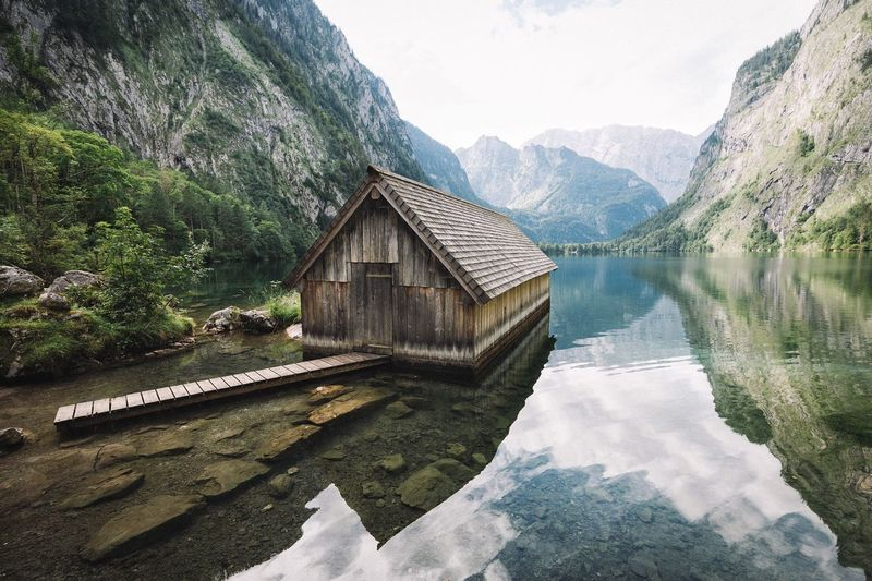 Boathouse in lake by mountains against sky