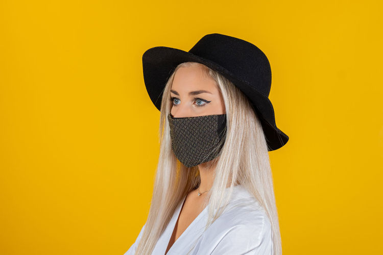 Portrait of young woman wearing mask and hat against yellow background