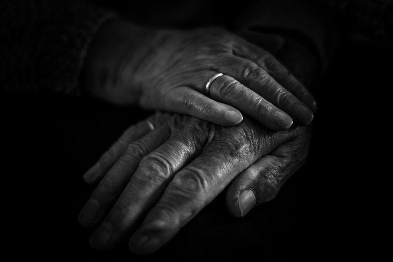 Cropped hands of senior couple against black background