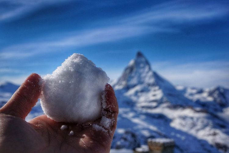 Cropped Image Of Hand Holding Snowball Against Sky