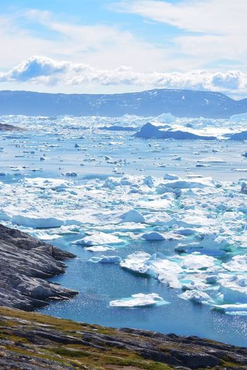 Ilulissat, Greenland, July | UNESCO world heritage site | impressions of Jakobshavn | Disko Bay Kangia Icefjord | huge icebergs in the blue sea on a sunny day | climate change - global warming Greenland Travel Destinations UNESCO World Heritage Site Iceberg Icebergs Ice Sea White Nature No People Day Scenics - Nature Outdoors Water Climate Change Global Warming Melting Glacier Idyllic Tranquility Cloud - Sky Tranquil Scene Outdoor Photography Wanderlust Scenery Scenics