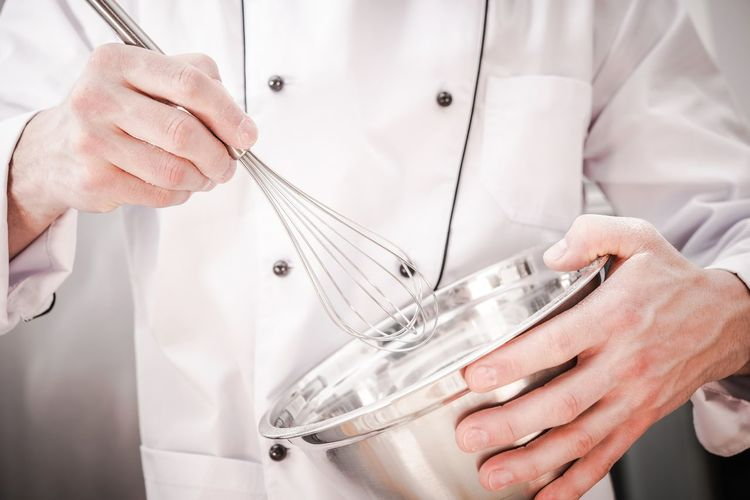 Midsection of chef holding wire whisk and bowl