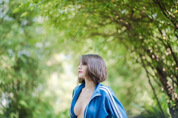 Sensuous female model standing against trees