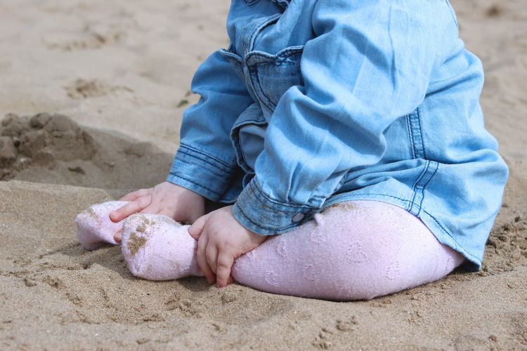 Low section of baby sitting on sand at beach