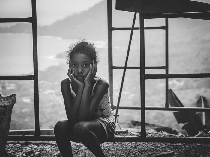 Portrait of teenage girl sitting on railing