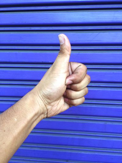 Close-up of hand showing thumbs up sign against blue shutter
