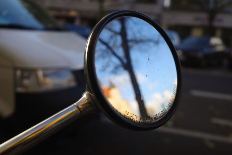 Close-up of eyeglasses on side-view mirror