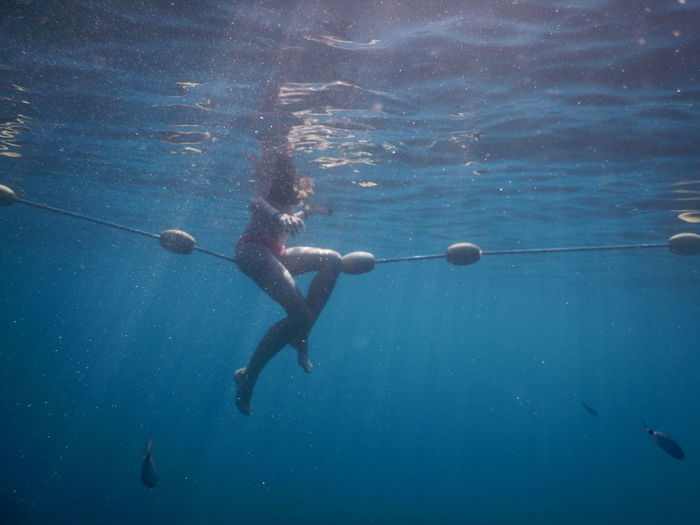 Low section of woman swimming undersea