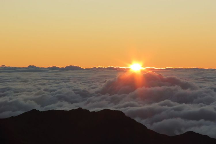 Sunrise at Haleakala Crater on Maui Sunset Scenics Tranquil Scene Beauty In Nature Mountain Tranquility Majestic Orange Color Atmospheric Mood Idyllic Atmosphere Nature Tourism Cloudscape Sun Environment Awe Mountain Peak Sunlight Covering Vulcano Crater Hawaii Maui
