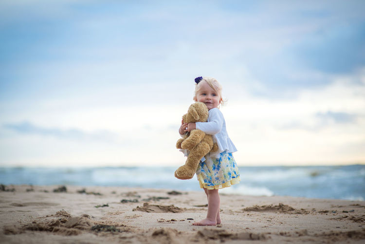 Cute girl holding stuffed toy while standing against sea at beach