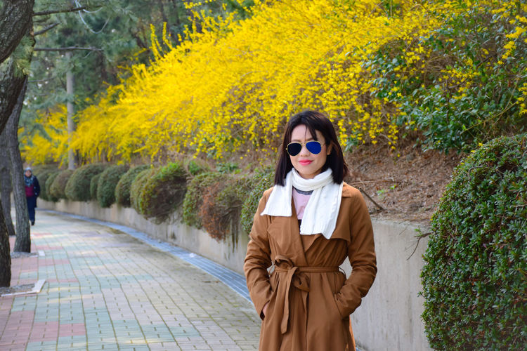 Tree Portrait Autumn Young Women Child Standing Looking At Camera Front View Hiker Trench Coat Growing Friend Scarf Leaf Vein Film Noir Style Shore Wearing Blooming Leaves Overcoat Jacket Footpath
