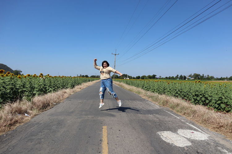 Happy woman jumping on road against clear blue sky
