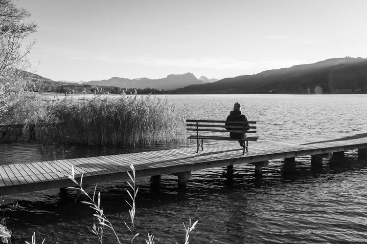 Rear view of man on pier over lake against sky