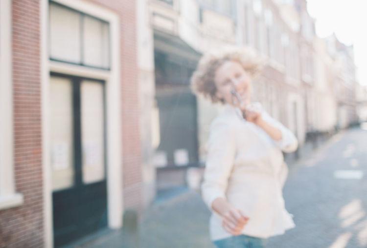 Defocused image cheerful woman walking on street in city