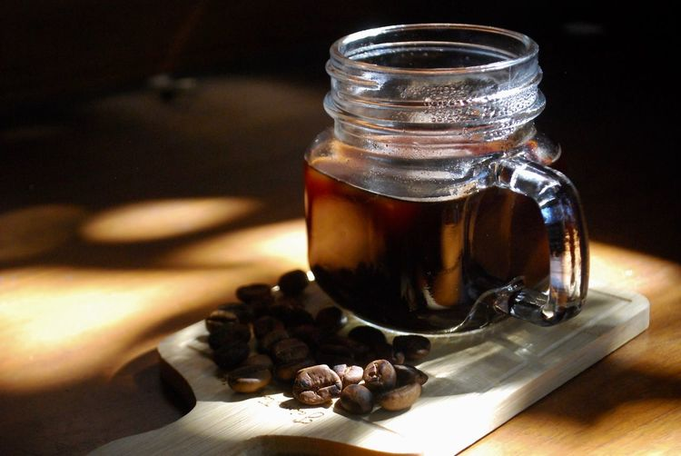 Close-up of drink by roasted coffee beans in jar on cutting board over table