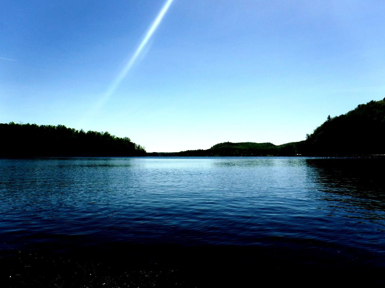 nature, beauty in nature, lake, water, tranquility, scenics, tranquil scene, silhouette, blue, outdoors, rippled, no people, clear sky, sky, tree, day