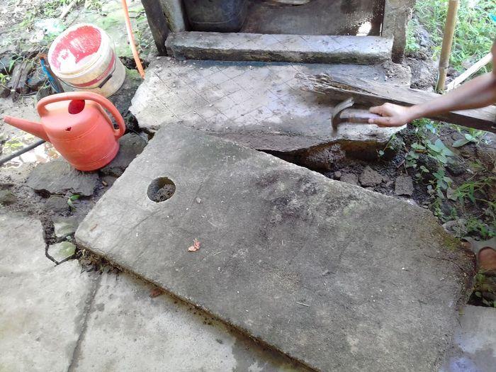 A man repair a toilet door. Repairing High Angle View Close-up Repairman Tool Hammer