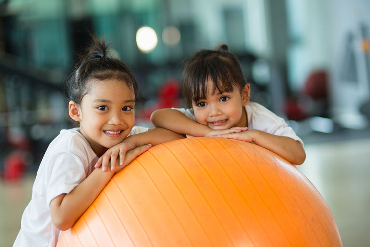 Portrait of girls over fitness ball in gym