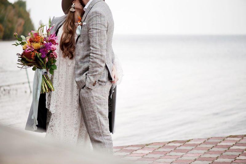 Bride and bridegroom kissing by sea