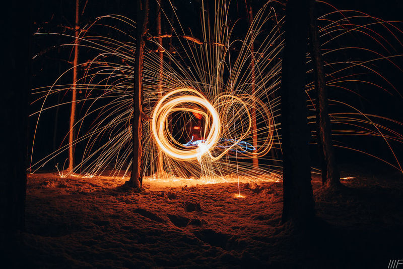 Night Long Exposure Motion Illuminated Blurred Motion Wire Wool Spinning Glowing Sign Burning Warning Sign Real People Light - Natural Phenomenon One Person Fire Orange Color Creativity Speed Fire - Natural Phenomenon Nature Sparks Light Trail Outdoors Skill  Light