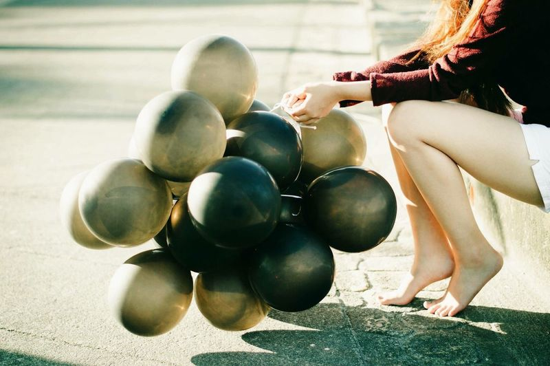 Low Section Of Woman Holding Balloons While Sitting On Roadside