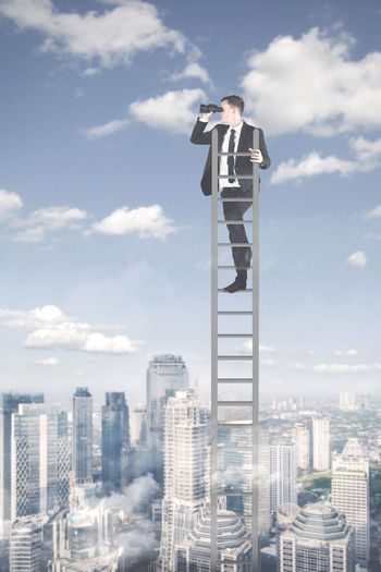 Digital composite image of businessman standing on ladder against sky