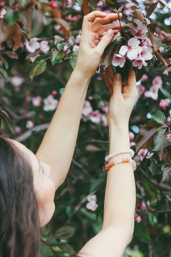 Low section of woman hand holding flowering plant