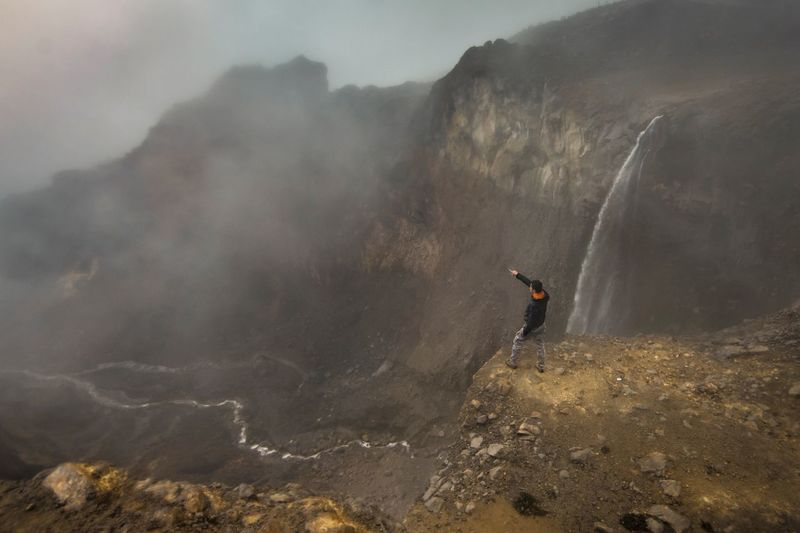 High angle view of man standing on mountain in foggy weather