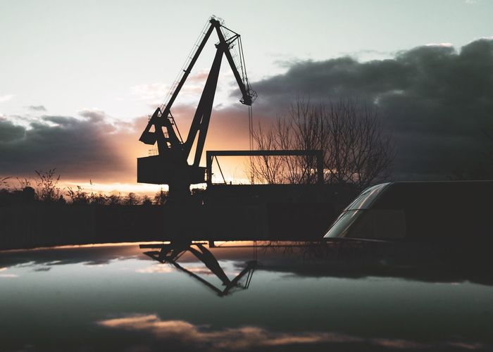 Silhouette crane by lake against sky during sunset