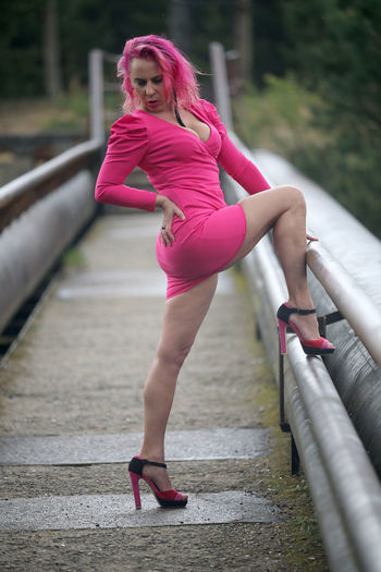 Full length of woman in pink shoes on railing
