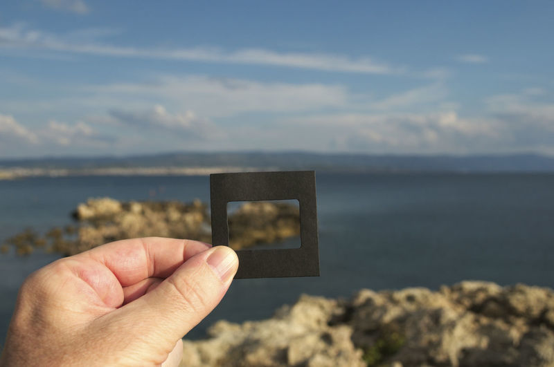 Cropped hand of person holding photographic slide against sea