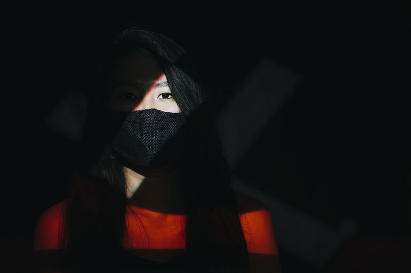 Portrait of woman covering face in darkroom