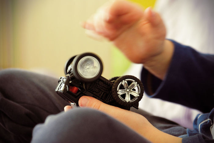 One Person Hand Human Hand Real People Lifestyles Leisure Activity Human Body Part Selective Focus Holding Sitting Technology Indoors  Body Part Men Time Relaxation Sofa Finger Boy Childhood Playing Toy Car Wheel Motion Rotation
