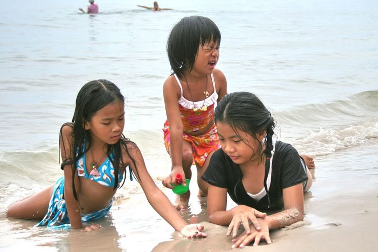 Girls playing on shore at beach