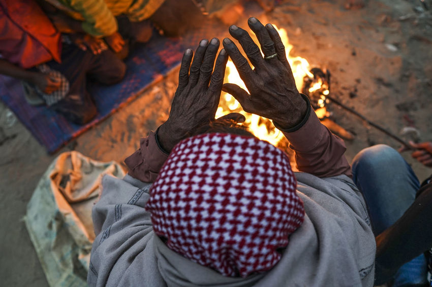 A man from the nearby slum warms his hand as the temperature dropped. Winter Close-up Cold Day Focus On Foreground High Angle View Keeping Warm Lifestyles Low Section Men Outdoors People Poverty Real People Spirituality Warmth Women Go Higher