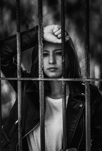 Portrait of young woman standing behind fence