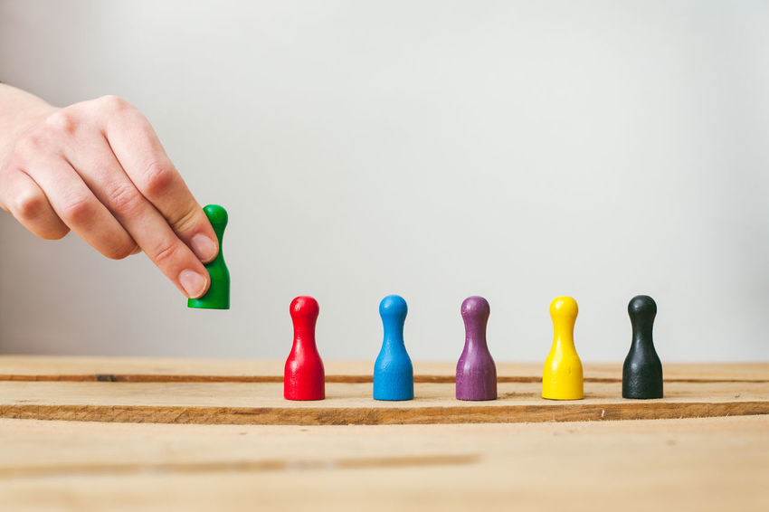 Business Team Building, diversity. Colorful pawns in a row representing a Diverse Workforce Business Diversity In A Row Teamwork Work Colorful Concept Conceptual Divers Hand Human Body Part Human Hand Ideas One Person Pawns Row Team