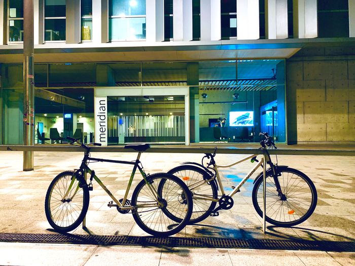 Bicycle parked on footpath by building