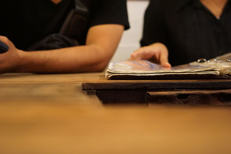 Midsection of people reading book on table