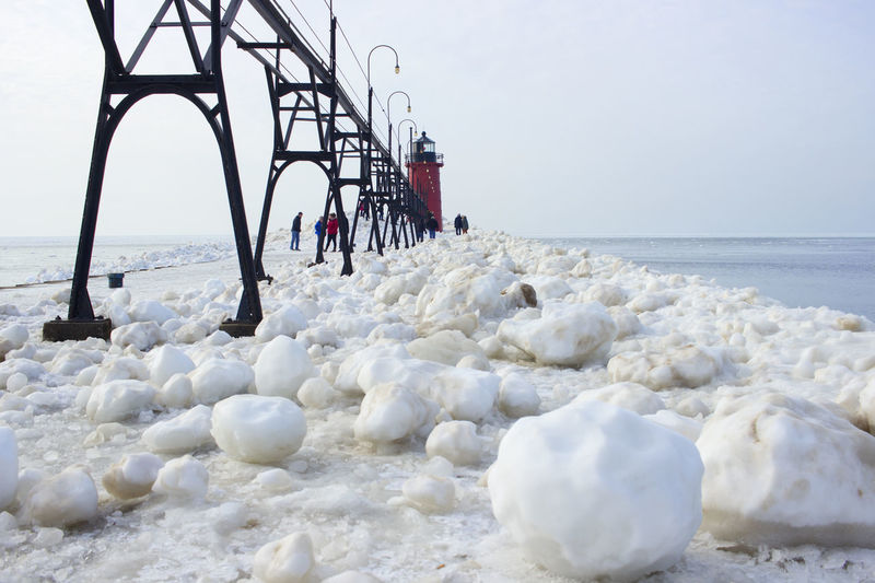 Snowballs On Pier Architecture Beauty In Nature Built Structure Circle Tour Cold Temperature Cold Winter ❄⛄ Day Horizon Over Water Ice Lake Michigan Landmark Landscape_photography Michigan Michigan Lighthouses Nature Outdoors People Pier Sky Snow ❄ Snowballs South Haven, Michigan Travel Destinations Water Weather