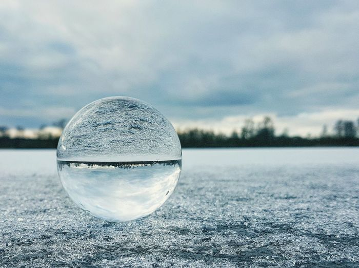Close-up of crystal ball on frozen lake against cloudy sky