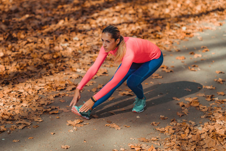 Woman stretching on footpath in park during autumn