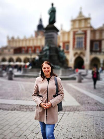 Portrait of smiling woman standing on walkway