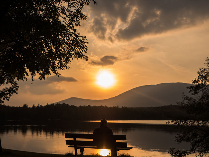 Alone Beauty In Nature Bench Bench Calm Chill Forrest Idyllic Lake Man Mountain Range Mountains Nature Non-urban Scene Orange Color Reflection Scenics Sitting Sky Standing Water Sun Sunset Tree Trees Water