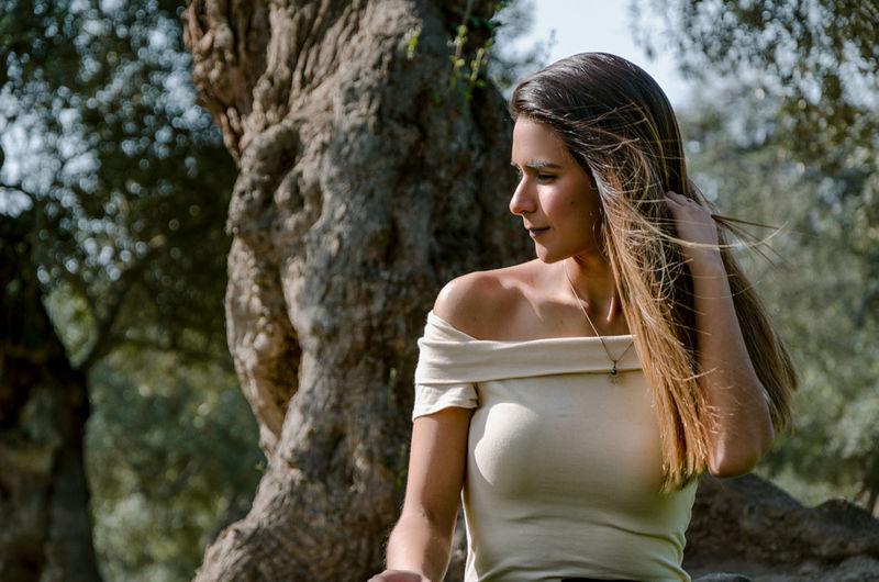 Young woman looking at tree