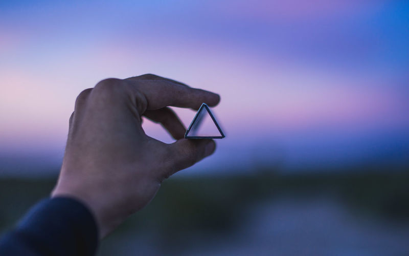Cropped Hand Holding Triangle Shape Structure Against Sky At Dusk