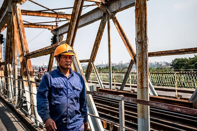 Portrait of smiling man standing against bridge